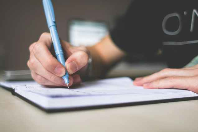 person holding blue ballpoint pen writing in notebook